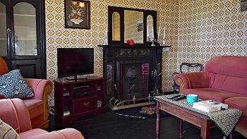 Le salon chaleureux avec TV et cheminée